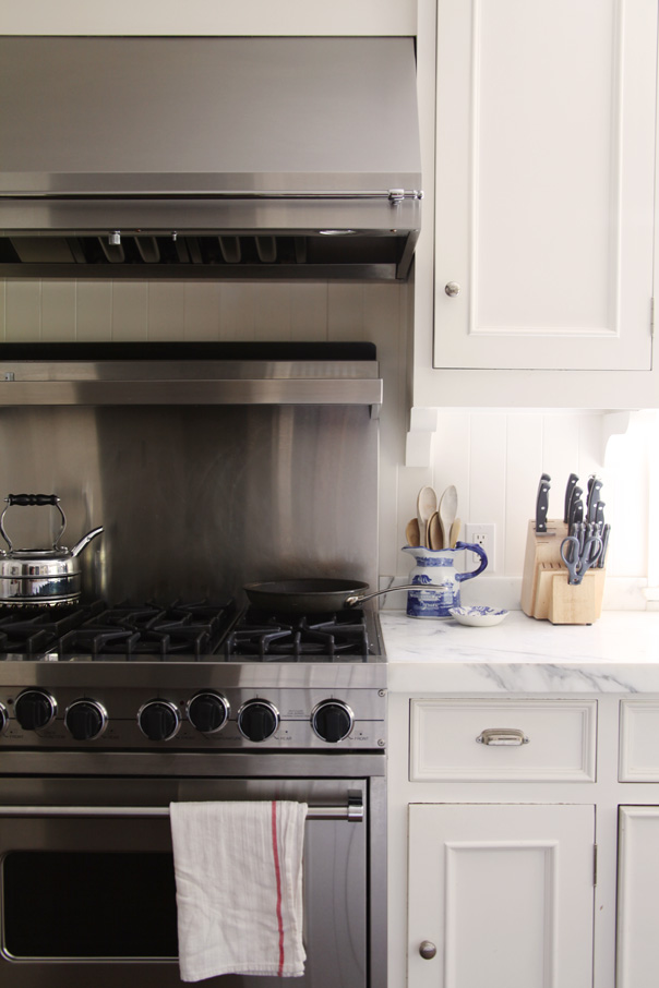 White Kitchen with Range Hood Stainless Steel Backsplash